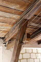 Obraz Stary strych. Dach z drewnianych belek i desek. Sznurki na bieliznę i lampa. - fototapety do salonu