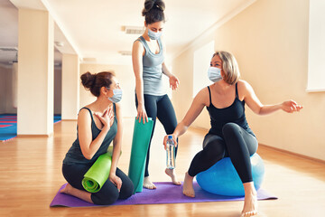 New normal. A group of young women in protective masks communicate in a yoga studio. The concept of...