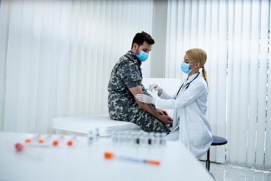 English soldier getting vaccine shot during corona virus pandemic. Military vaccination and immunization.