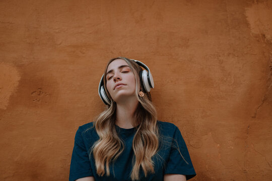 Young mindful blonde female with closed eyes listening to song in wireless headset on brown background in city