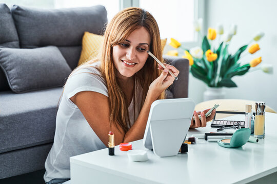 Happy young female in casual outfit looking at mirror and applying makeup on eye at home