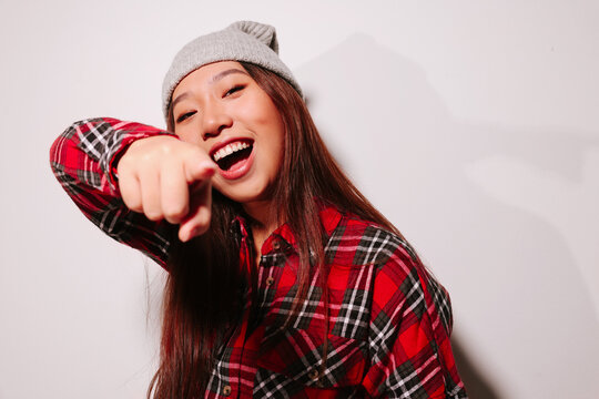 Close-up portrait of cheerful Asian young woman pointing at camera with finger