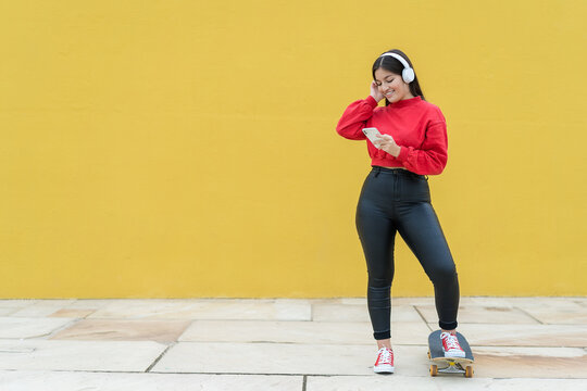 Young cheerful ethnic sportswoman listening to music from headset while watching cellphone and standing on street with skateboard on yellow background