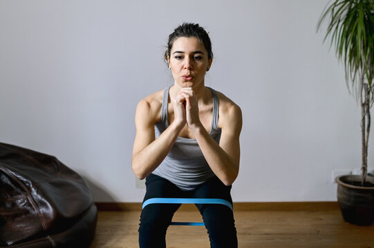 Adult active female athlete working out with hands clasped while leaning forward with resistance band and looking down in house