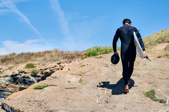 Back view full length of anonymous man wearing surfing suit walking through rocky coast