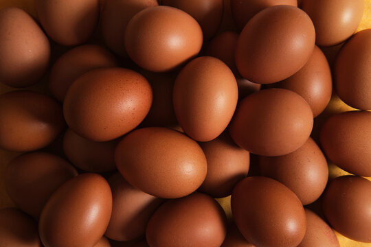 From above of full frame background of heap of raw brown chicken eggs