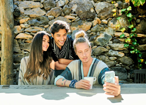 Young glad multiethnic partners taking self portrait on photo camera at table against climbing plants in courtyard