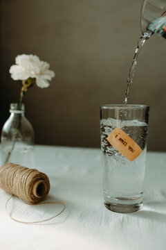 Water pouring into glassware with inscription i miss you placed near skein of thread and blooming carnation