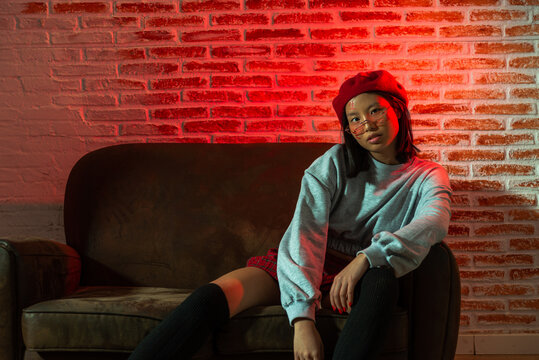 Full length confident young Asian female in stylish outfit and hat sitting on couch and looking at camera in dark room against brick wall