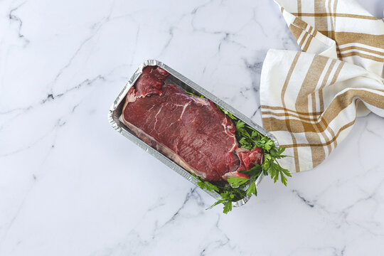 Top view of ready to cook meat beef steak with parsley in foil container on marble table