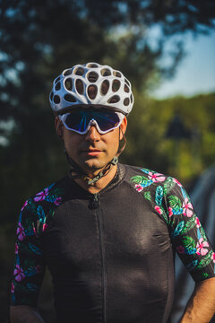 Confident young male cyclist in sportswear and protective helmet and sunglasses standing green trees after training in park on sunny day