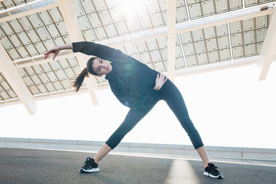 Positive fit young female in black sportswear stretching arms while warming up on sunny road in suburb and looking away contentedly