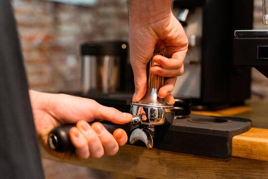 Crop unrecognizable barista pressing coffee in portafilter with tamper while preparing beverage in cafe