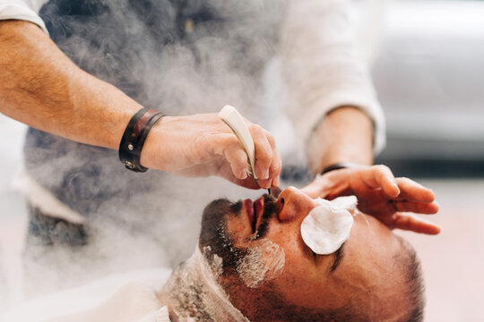 Crop anonymous beauty master shaving beard of client with straight razor during steam vapor treatment in hairdressing salon