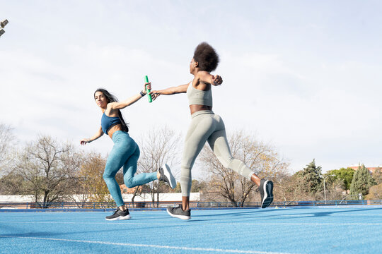 Fit multiracial female athletes passing baton while running along track at stadium during relay race