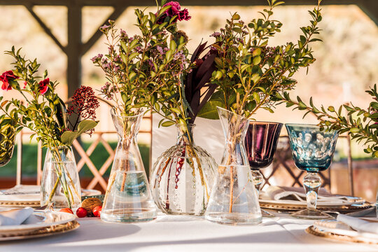 Close-up of transparent glass vases with bunches of fresh flowers placed on table for event