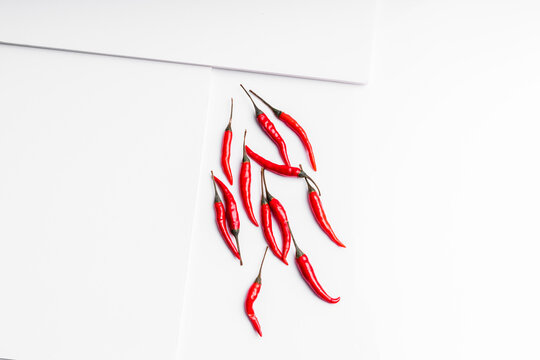 High angle composition of hot red chili peppers arranged plate against white board surface background