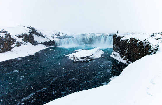 Distant view of explorer standing on edge of cliff and admiring scenery of waterfall in winter in Iceland