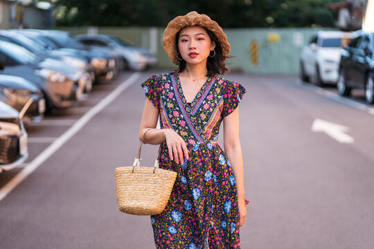 Asian female in straw hat and with wicker handbag standing on parking lot and looking at camera