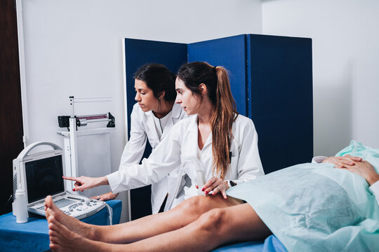 Two female doctors are making an ultrasound to the legs of a patient that is lying on a stretcher in an hospital