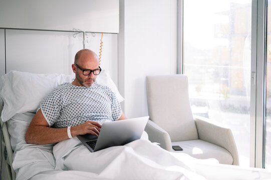 Concentrated adult male patient in hospital gown and glasses browsing netbook while lying on bed in light ward in clinic