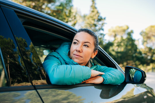 Low angle of content female sitting on passenger seat in modern shiny car and looking out of window