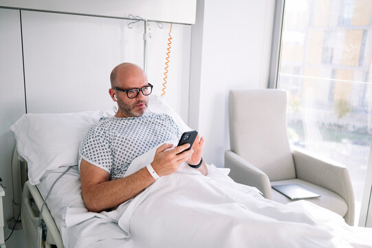Concentrated adult male wearing patient gown and eyeglasses browsing phone on bed in light ward in modern hospital