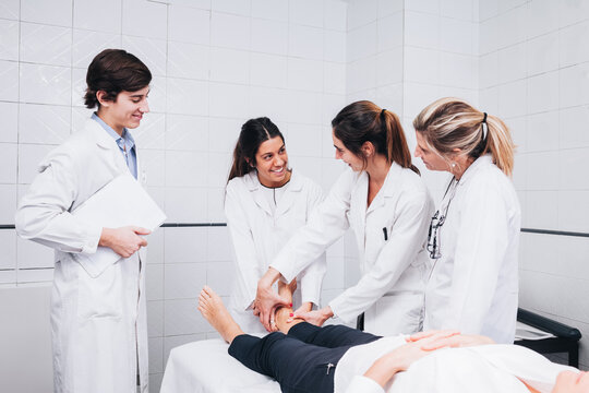 A group of doctors are examining the leg of a patient that is lying on a stretcher while are smiling and looking one each other on an hospital room while one is holding an x-ray