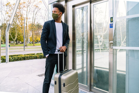 African American male tourist with suitcase and in protective mask standing near of elevator in airport while traveling during coronavirus pandemic
