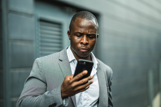 Serious black male boss browsing a cellphone in town