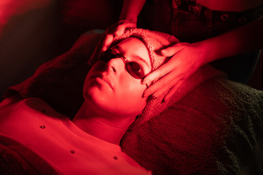 From above of crop anonymous female cosmetologist adjusting protective goggles of relaxed young woman lying on couch during red LED light facial therapy in professional salon
