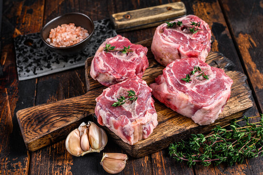 Raw mutton lamb neck meat on a butcher board with cleaver. Dark wooden background. Top view