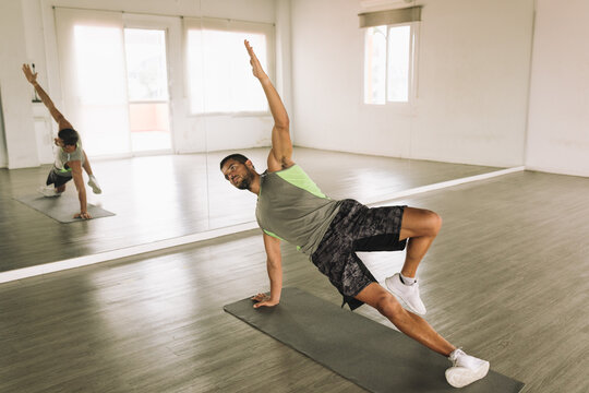 Full body of young focused fit determined sportsman in activewear performing High Side Plank with leg raises exercise during workout in studio near big wall mirror