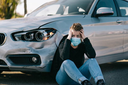 Sad young female driver in casual clothes and medical mask sitting on road near expensive damaged car and crying after accident during coronavirus outbreak