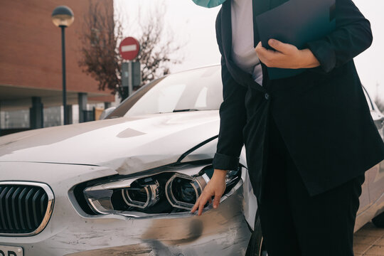 Cropped unrecognizable female insurance agent in formal outfit and protective mask writing protocol near damaged car parked on street after accident