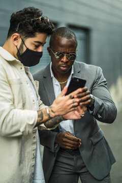 Stylish African American male executive un suit near ethnic partner in mask watching cellphone on city street
