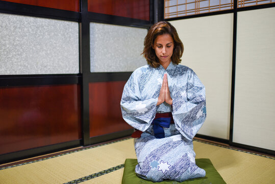 Interior portrait of kneeling young attractive caucasian woman with hands in prayer wearing a traditional Japanese kimono inside a house, Ainokura, Japan