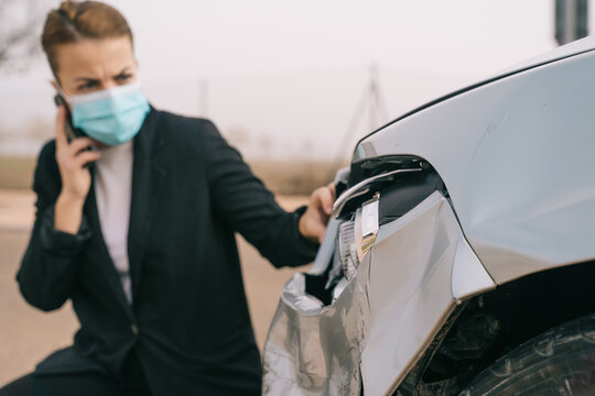 Unrecognizable young female driver in casual clothes and face mask talking on mobile phone while standing near modern damaged car after accident on city road