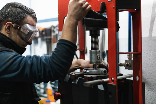 Side view of attentive adult male auto mechanic in protective goggles operating hydraulic press while installing cars bearings