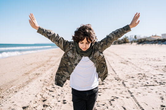 Portrait of boy walking on the beach in winter on a sunny day