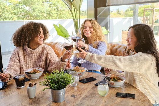 Cheerful multiracial young women in casual clothes toasting with glasses of wine while gathering at table and having dinner together in restaurant