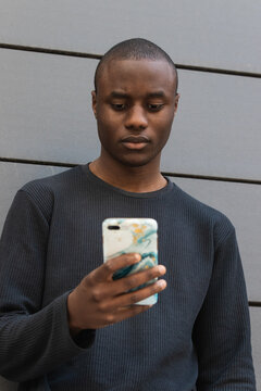 Attentive African American male scrolling modern mobile phone while standing against gray building