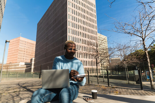 Confident self employed African American guy in trendy outfit and eyeglasses typing on laptop while working remotely in city park sitting on bench with takeaway coffee and notebook