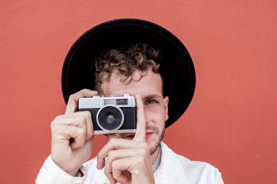 Confident young male with curly hair in trendy clothes and hat smiling while taking photo on retro film camera against red background