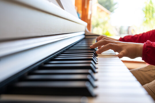 Cropped anonymous child playing piano while reading notes and rehearsing song at home