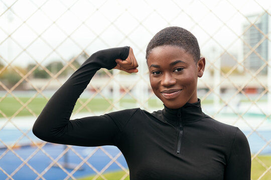 Young content African American female with short hair looking at camera while raising arm in city