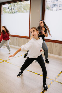 Group of young women and girls rehearsing hip hop dancing movements while practicing in spacious hall together during active lesson with instructor