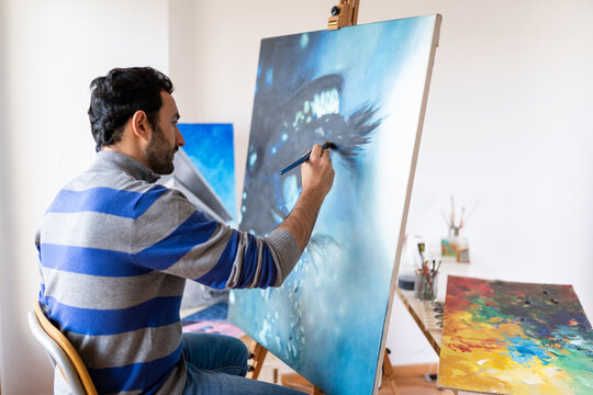 Side view of young bearded ethnic painter in casual wear siting in a chair painting with brush on canvas in art studio
