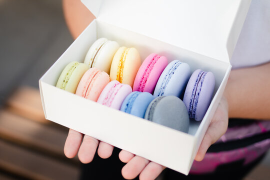 Multicolored sweet macarons or macaroon flavored cookies in a paper box
