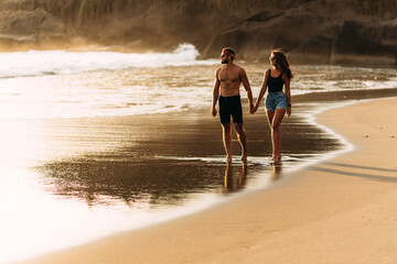 A happy couple walks along a sandy beach on the island of Bali. Couple in love at sunset by the...
